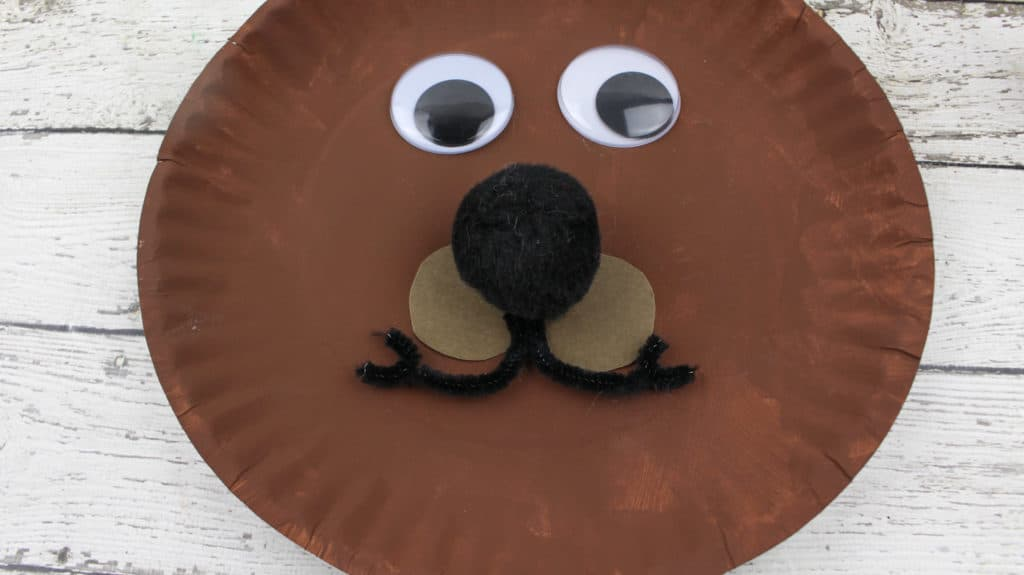 2.  For the nose, generously apply glue to the back of the pom-pom and attach to the paper plate.  3.  Apply glue to the back of the two nickel-size brown circles and place underneath the pom pom nose, side by side.